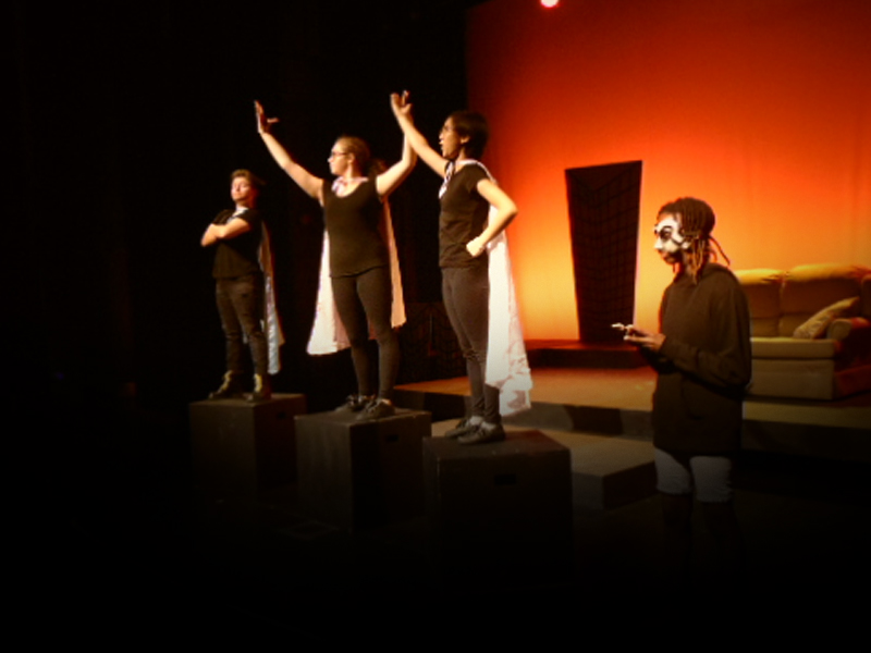 Four youth performers on stage in front of a bright orange back drop. Three of them stand on boxes wearing capes in various superhero poses. The other one stands near by wearing a mask made of question marks holding a cellphone.